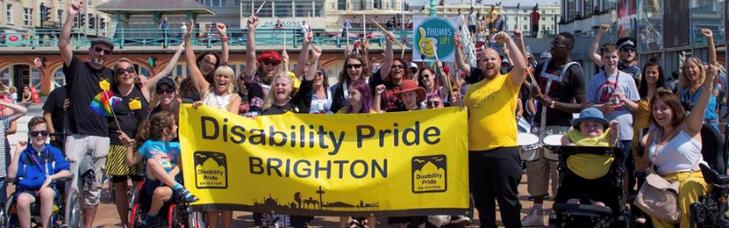 Image of people gathered in Brighton holding a Disability Pride Brighton banner