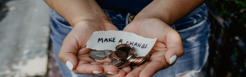An image of a person holding their hands out with a note that reads 'Make a Change' and some coins.
