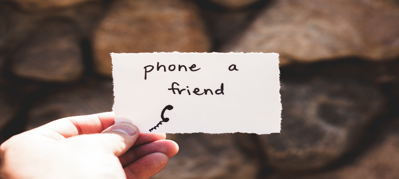 Image of a person holding out a note that reads 'Phone a friend'