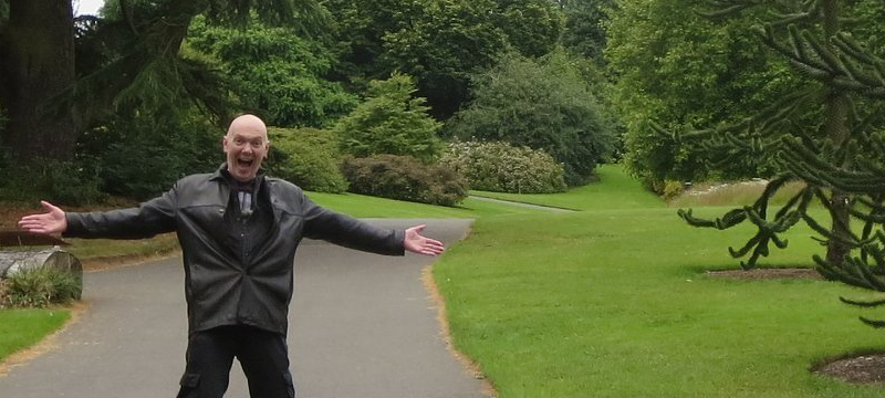 Image of Steve posing with arms stretched out in a green space.