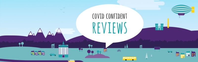 "Generic cityscape with a speech bubble. Test in the speech bubble reads ""Covid Confident reviews""."