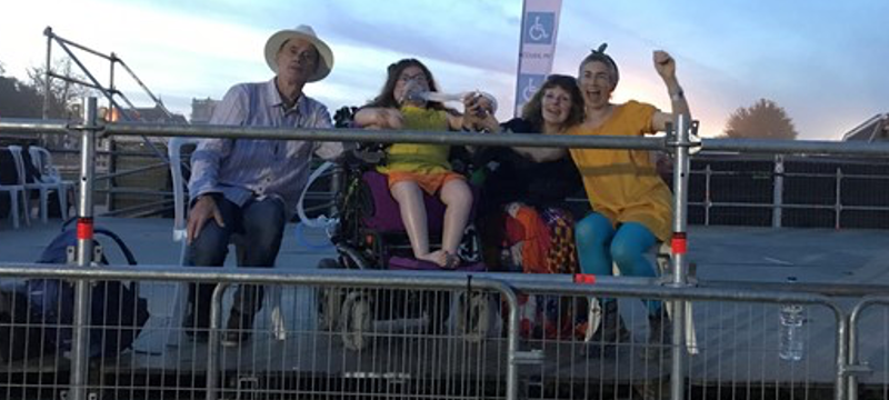 Four people sitting on a viewing platform at an outdoor music festival.