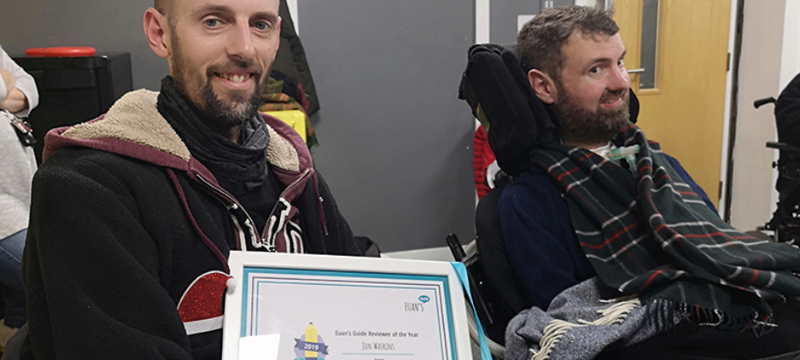 Euan's Guide Ambassador Jon (left) sitting next to Euan (right). Jon is holding a framed certificate.