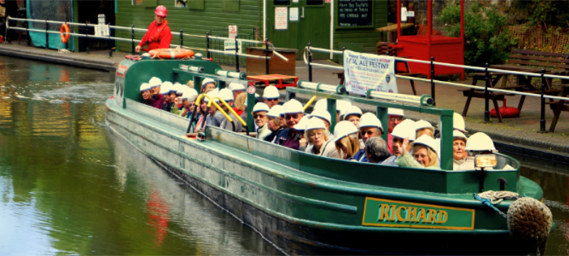 A green narrowboat filled with people wearing white helmets on a canal.