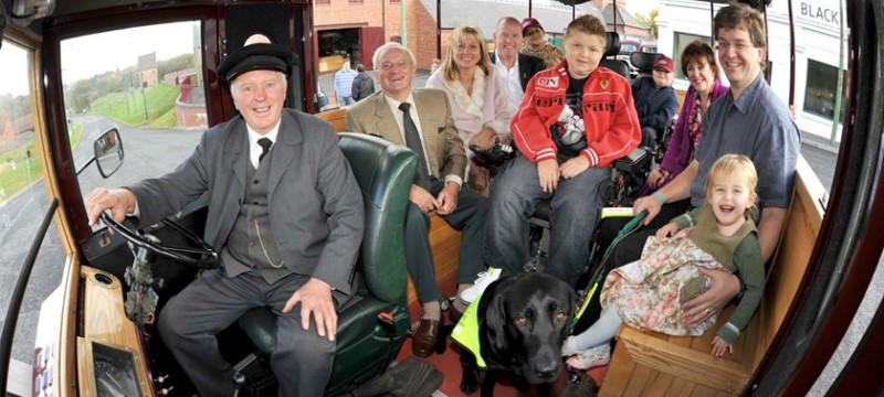 An old fashioned bus filled with people, including wheelchair and powerchair users and an assistance dog.