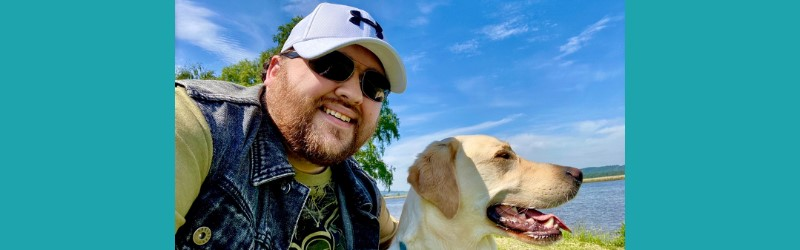 A picture of Jonathan wearing sunglasses and a cap next to his guide dog Sam. A blue sky can be seen in the background of the image. The image is against a teal background.