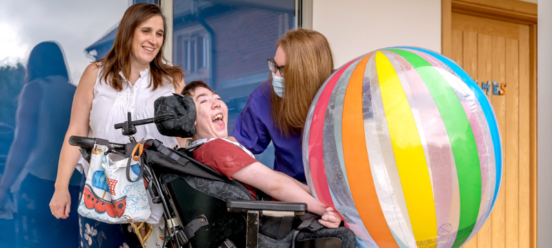 James smiling in the centre of the image with a large colourful ball. Christine (left) and Helen (right) pictured behind him.