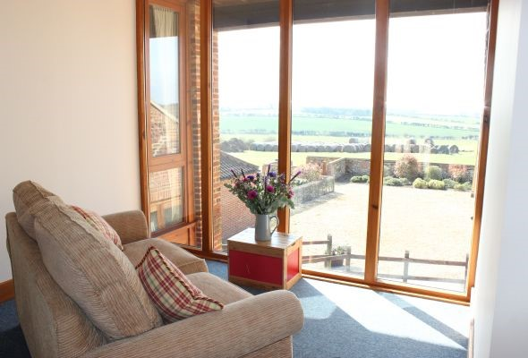 A photo of a room with large windows overlooking the countryside.