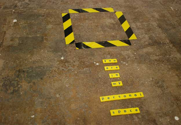 A photo of some writing on the floor which reads 'you're in my personal space',