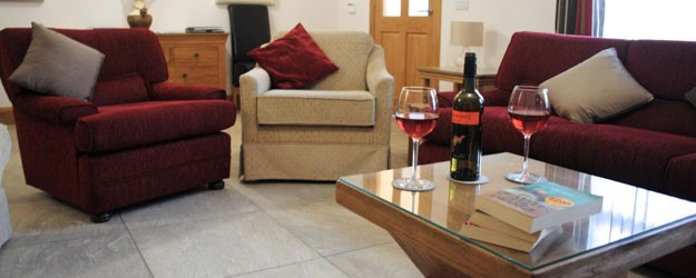 A photo of a living room with a bottle of wine on the table.