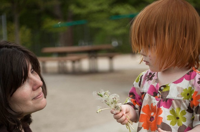 A photo of a child giving a woman a flower.