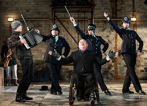 Photo of wheelchair user singing centre stage with four policemen behind him