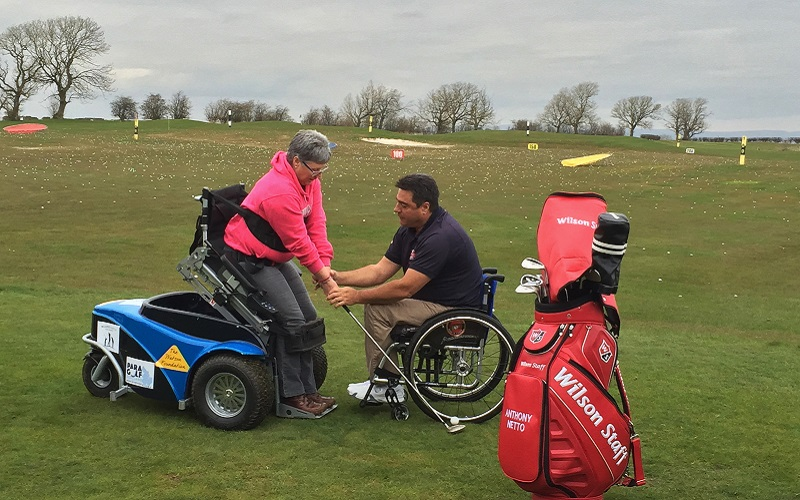 Photo of Anthony Netto and a lady using the paragolf machine.