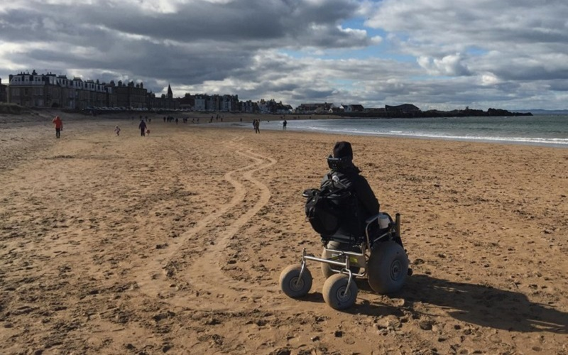 Photo of a wheelchair user at the beach.