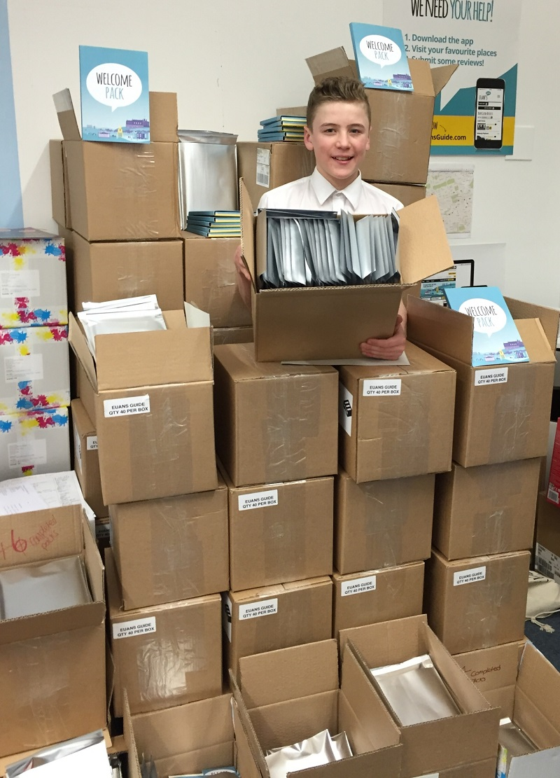 Photo of our volunteer Lewis surrounded by boxes.
