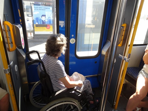 The wheelchair space on one of the older trams. The button to alert the driver that you wish to get off is on the blue door, and one of the pink pads on which you touch your chipkaart is just behind the wheelchair.