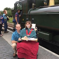 Wheelchair user with husband in front of a steam locomotive