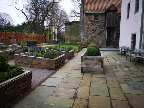 Paving section of the garden with bench seating on the right
