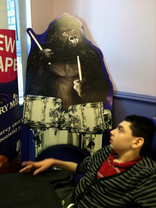 Picture of John-Luke looking at the standup poster at Cadbury World of the gorilla playing the drums