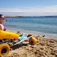 Sitting in a beach wheelchair on the beach in Barcelona