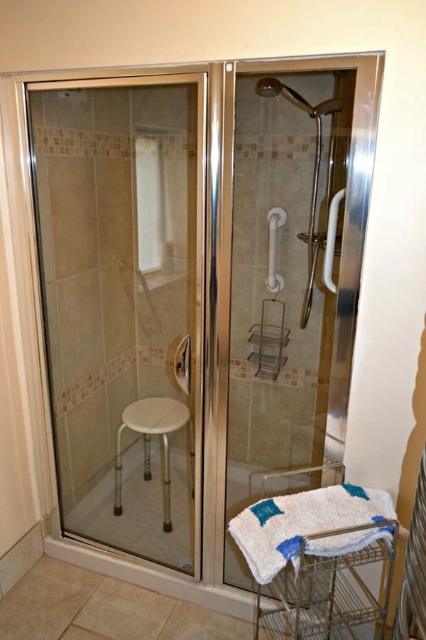 Shower with one small step, grab bars and seat.