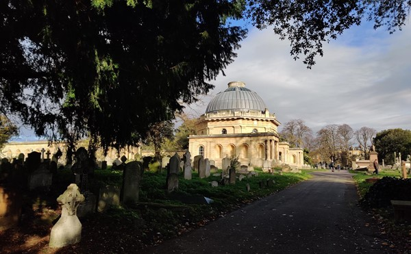 A view of the domed chapel in sunshine, framed by shaded trees in the foreground.